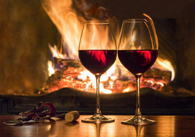 Two glasses of red wine in front of a fireplace — Stock Photo