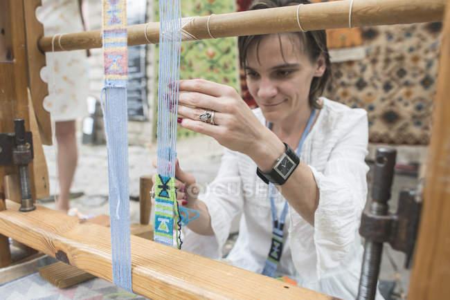 Vista cortada de mulher tecelagem tapete com tear tecelagem — Fotografia de Stock