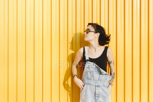 Junge Frau steht vor gelber Wand — Stockfoto