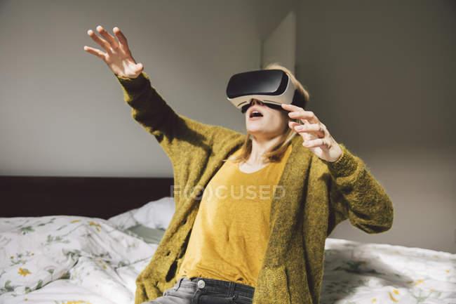 Awed donna indossando occhiali di realtà virtuale utilizzando le mani — Foto stock