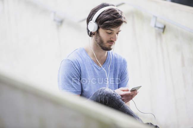 Молодой человек слушает музыку в наушниках и смотрит на смартфон — стоковое фото