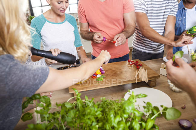 Freunde in der Küche arrangieren Spieße auf Holztablett — Stockfoto