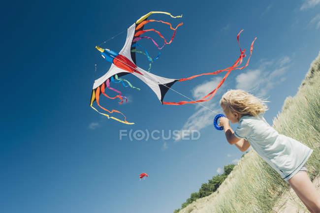 Хлопчик холдингу flying кайт пляжі dune — стокове фото