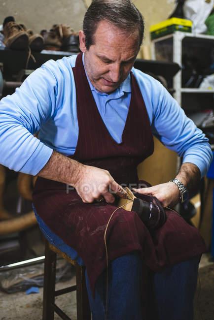 Shoemaker repairing shoe in workshop — Stock Photo