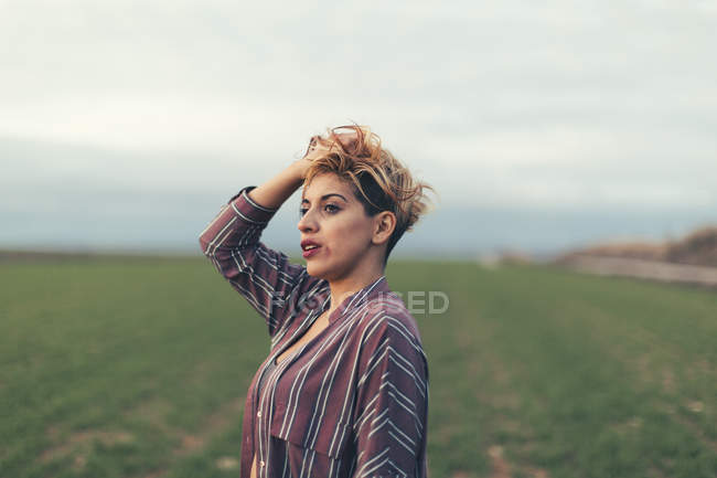 Portrait of woman with hand in her hair on a field — Stock Photo
