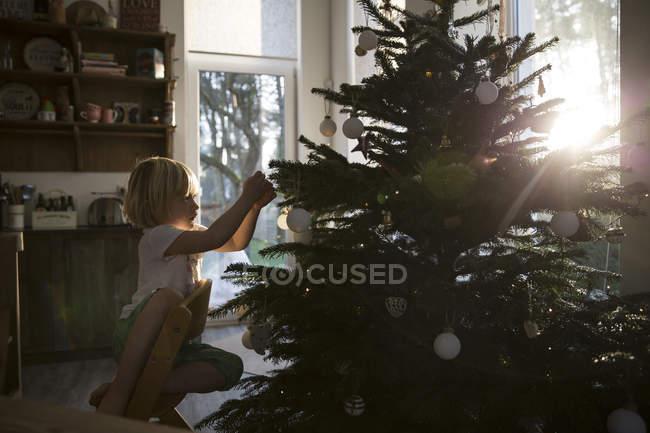 Girl decorating Christmas tree in backlight — Stock Photo