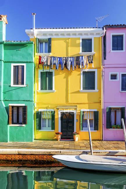 Découvre à trois maisons colorées à la lumière du soleil, Burano, Vénétie, Italie — Photo de stock