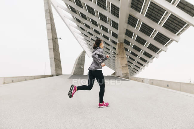 Woman jogging under solar panel — Stock Photo