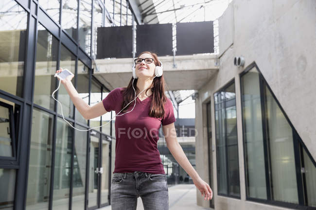 Portrait of young woman listening music with smartphone and headphones — Stock Photo