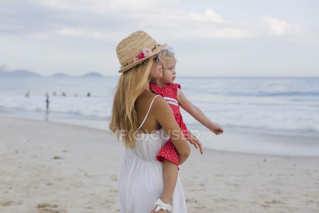 Brasil, Ріо-де-Жанейро, матері, несучи дочка на всесвітньо відомому пляжі Копакабана — стокове фото