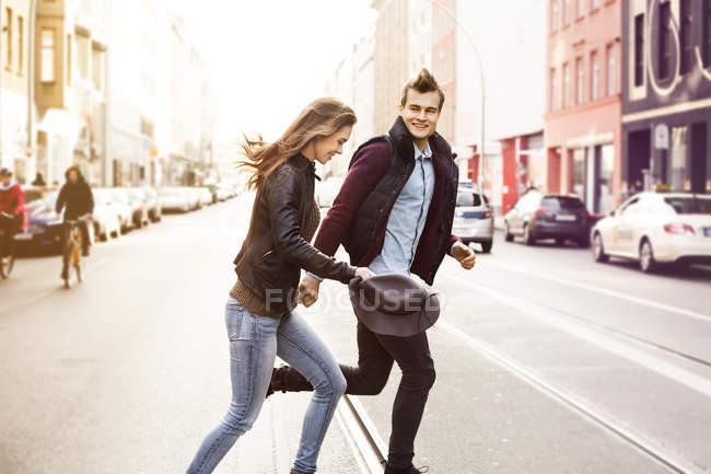 Germany, Berlin, happy couple crossing a street — Stock Photo