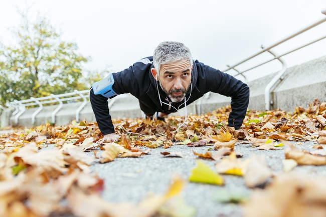 Человек делает отжимания в окружении осенних листьев — стоковое фото