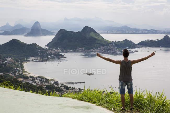 Brazil, Rio de Janeiro, tourist standing at view point, raising arms — Stock Photo