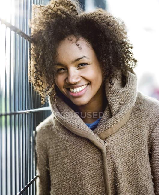 Портрет усміхнений молода жінка притулившись паркан — стокове фото