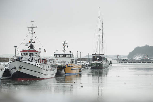 Germany, Sassnitz, Fishing boats in harbour in winter during daytime — Stock Photo