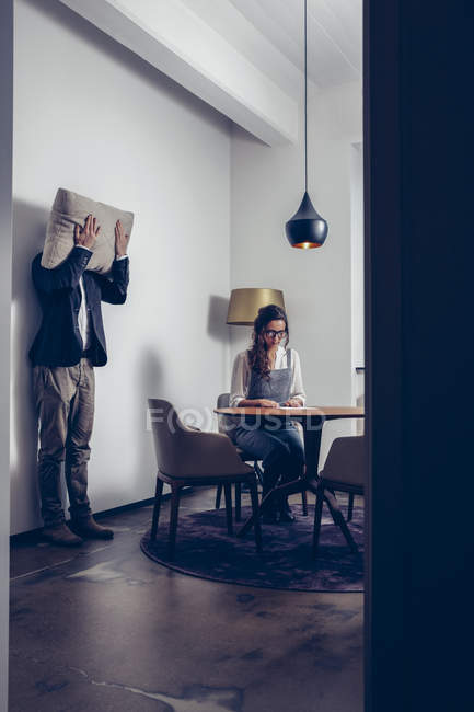 Young woman sitting at table with man standing at a wall covering his face with a cushion — Stock Photo