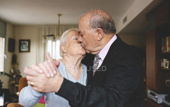 Старшая пара целуется и танцует дома — стоковое фото