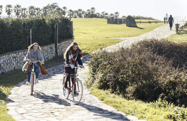 Dos mujeres jóvenes que andan en bicicleta a lo largo de la ruta - foto de stock