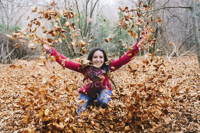Woman throwing autumn leaves in the air — Stock Photo