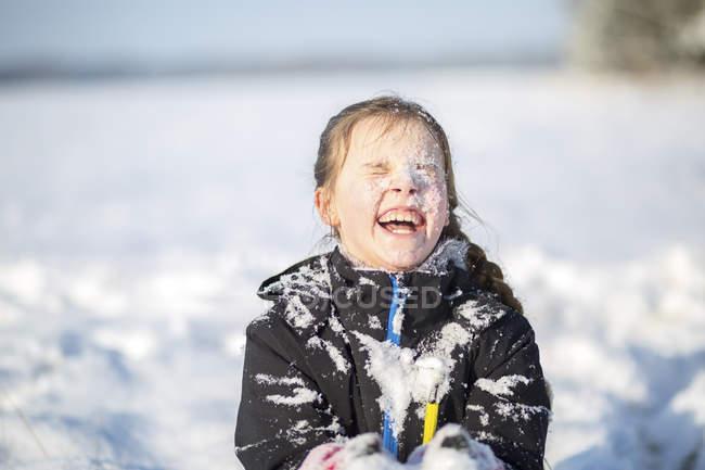 Портрет смеющейся девушки с заснеженным лицом — стоковое фото
