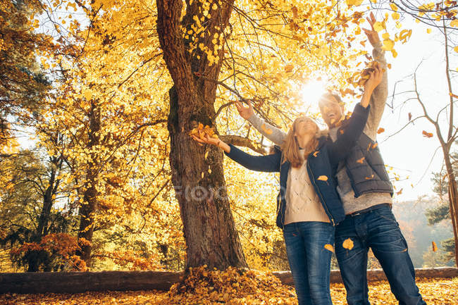 Couple having fun in autumn in forest — Stock Photo