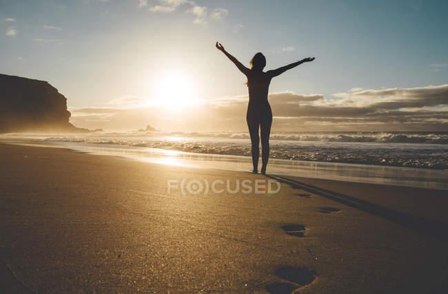 Женщина, стоящая на пляже с поднятыми руками на закате — стоковое фото