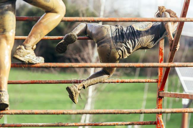 Participantes en la carrera de obstáculo extrema escalada sobre cañizo - foto de stock