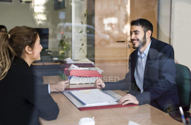 Young man and woman in office smiling at each other — Stock Photo