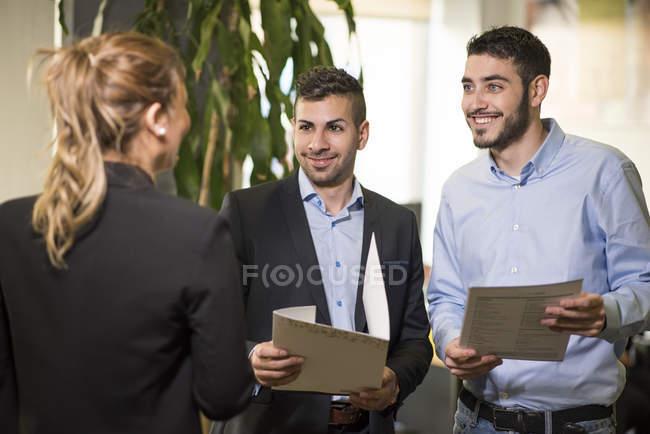 Три усміхнений колег у відділенні, Холдинг документів — стокове фото