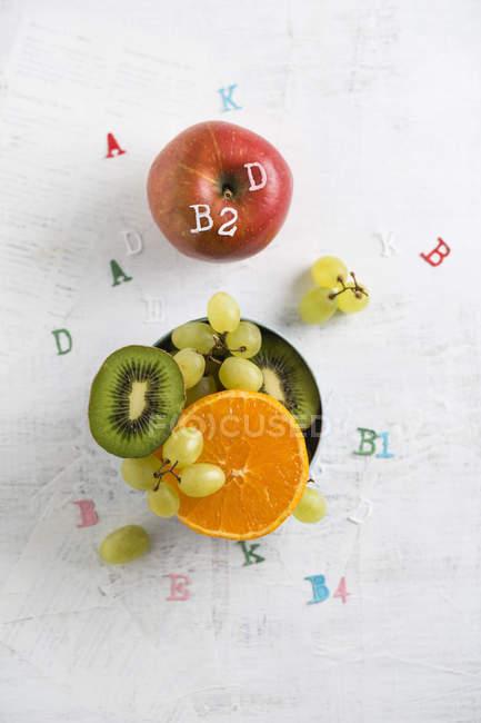 Plátano, manzana, naranja, kiwi y uvas verdes, diferentes vitaminas - foto de stock