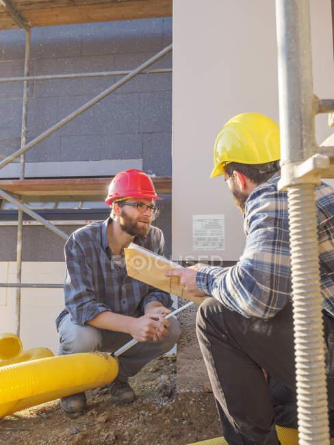 Ремесленники обсуждении в строительной площадки — стоковое фото