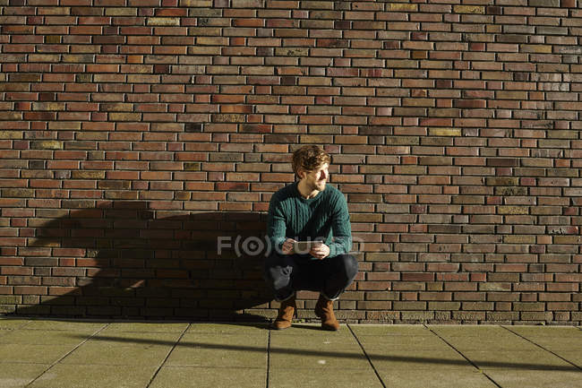 Young man crouching in front of a brick wall with digital tablet — Stock Photo
