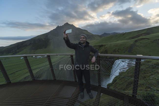 Islande, L'homme prend selfie à la cascade Skogafoss — Photo de stock