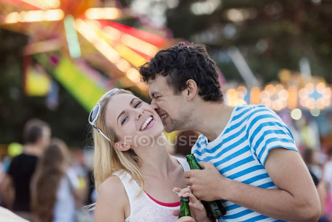 Coppia felice al divertimento fiera, baciare e tenere bibita — Foto stock