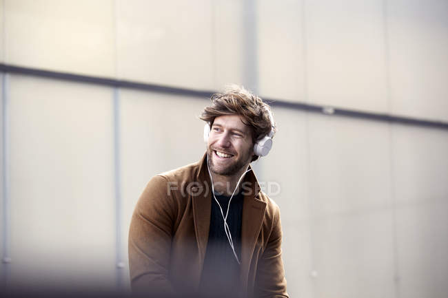 Smiling young man listening music with headphones at backlight — Stock Photo