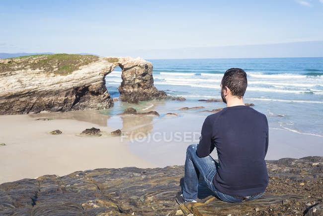 Spain, Ribadeo, back view of man sitting on rocks of Playa de Las Catedrales — Stock Photo