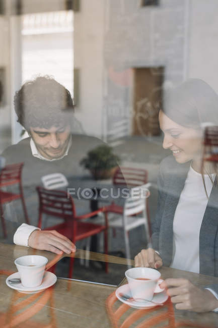 Two colleagues in a cafe looking at digital tablet — Stock Photo