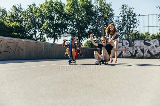 Three playful teenage friends having fun with scooter and skateboard — Stock Photo