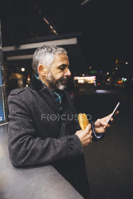 Man with Cheese Carniolan sausage and smartphone at street in night — Stock Photo