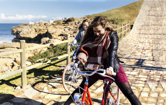 Dos mujeres jóvenes felices, andar en bicicleta a lo largo de la ruta - foto de stock