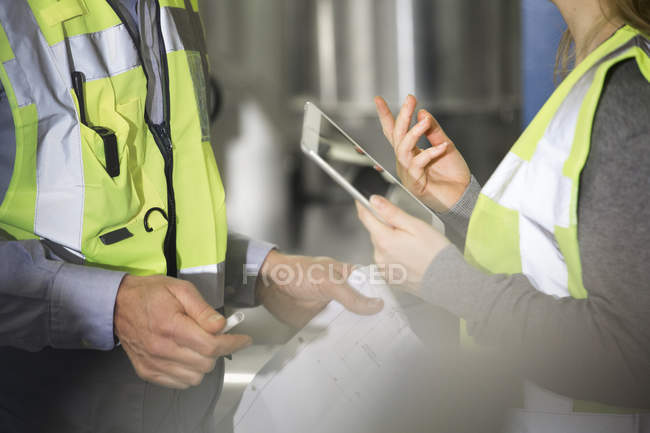 Colleagues wearing reflective vests talking in industrial plant — Stock Photo