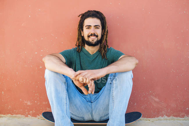 Portrait of smiling young man with dreadlocks and beard sitting on his skateboard in front of a reddish wall — Stock Photo