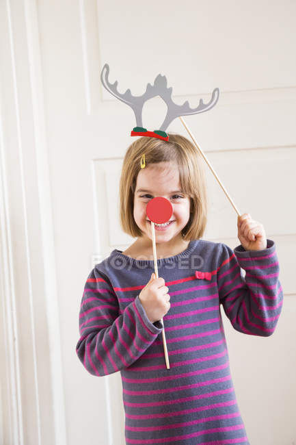 Portrait of girl with toy antlers and red nose — Stock Photo