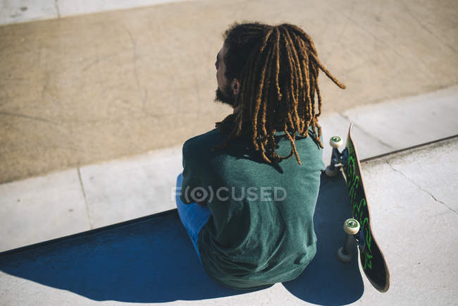 Back view of young man with dreadlocks sitting in a skatepark — Stock Photo