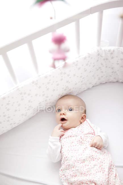 Девочка лежит в постели, ищет игрушку. — стоковое фото
