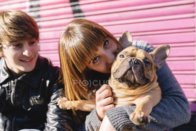 Portrait of young woman kissing French bulldog — Stock Photo