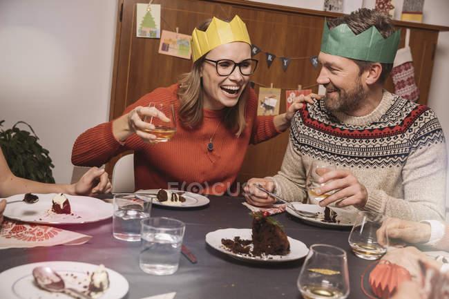 Щаслива пара вінцями паперу, сміючись маючи Різдвяна вечеря — стокове фото