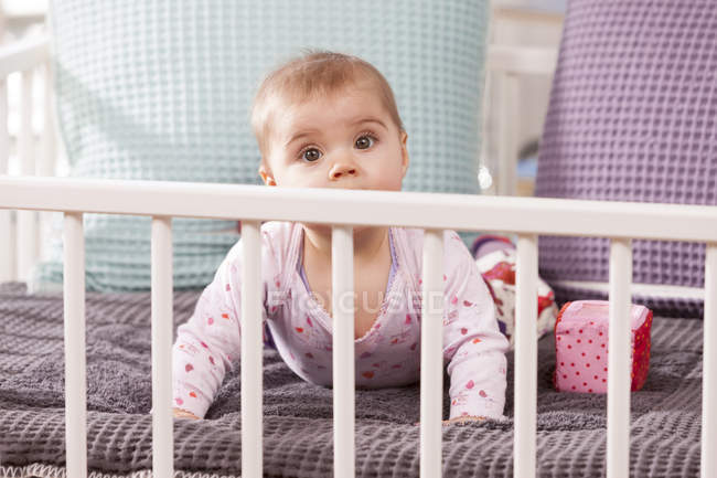Baby girl crawling in playpen — Stock Photo