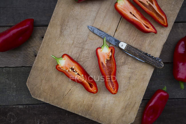 Chopped red pointed pepper on chopping board, halved, pocket knife — Stock Photo