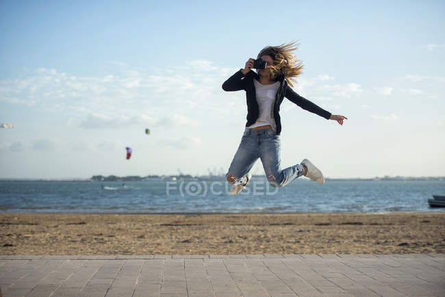 Женщина фотографирует во время прыжка в воздух — стоковое фото